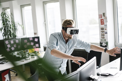 Businessman wearing VR glasses in office - JOSF02031