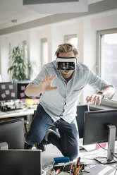 Businessman wearing VR glasses in office pretending to be a lion - JOSF02034