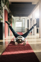 Businessman lying on carpet on the floor wearing VR glasses exercising - JOSF02037