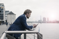 Businessman using cell phone at the riverside - JOSF02052