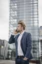 Businessman on cell phone in the city - JOSF02055