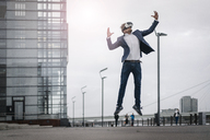 Businessman wearing VR glasses jumping in the city - JOSF02058