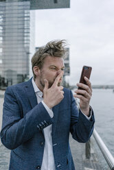Businessman with cell phone picking nose - JOSF02061