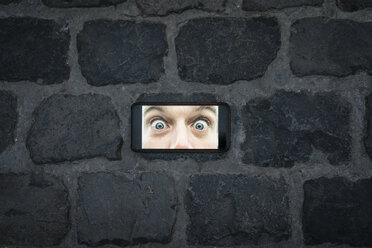 Cell phone image with eyes wide open on cobblestone pavement - JOSF02064