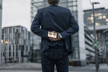 Businessman holding cell phone with image of eyes behind his back - JOSF02067