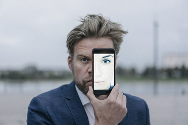 Businessman holding cell phone with image of a woman in front of his eyes - JOSF02070