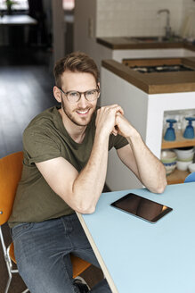 Portrait of smiling man with tablet in kitchen at home - PESF00752