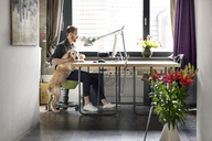 Man with dog working at desk at home - PESF00758