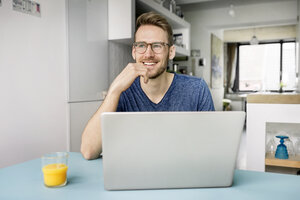 Portrait of smiling man using laptop in kitchen at home - PESF00761