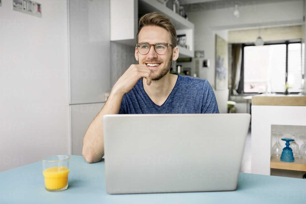 Portrait of smiling man using laptop in kitchen at home - PESF00761 - Peter Scholl/Westend61