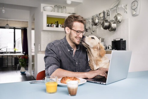 Smiling man with dog using laptop in kitchen at home - PESF00764