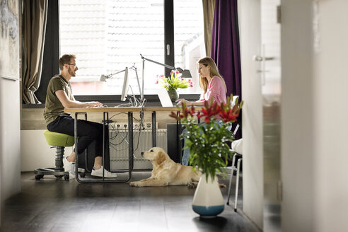 Man and woman with dog working at desk at home - PESF00767