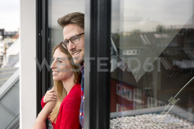Smiling young couple looking out of window - PESF00773
