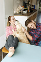 Happy young couple playing with dog at home - PESF00782
