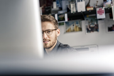 Portrait of young man behind computer screen at desk at home - PESF00785