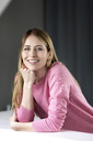 Portrait of smiling young woman wearing pink pullover - PESF00791