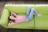 Smiling young woman lying on the couch - PESF00797