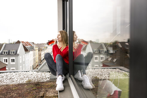Smiling young woman sitting at the window in city apartment having a drink - PESF00803