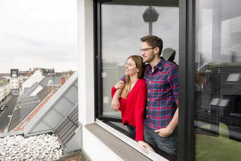 Smiling young couple looking out of window in city apartment - PESF00809