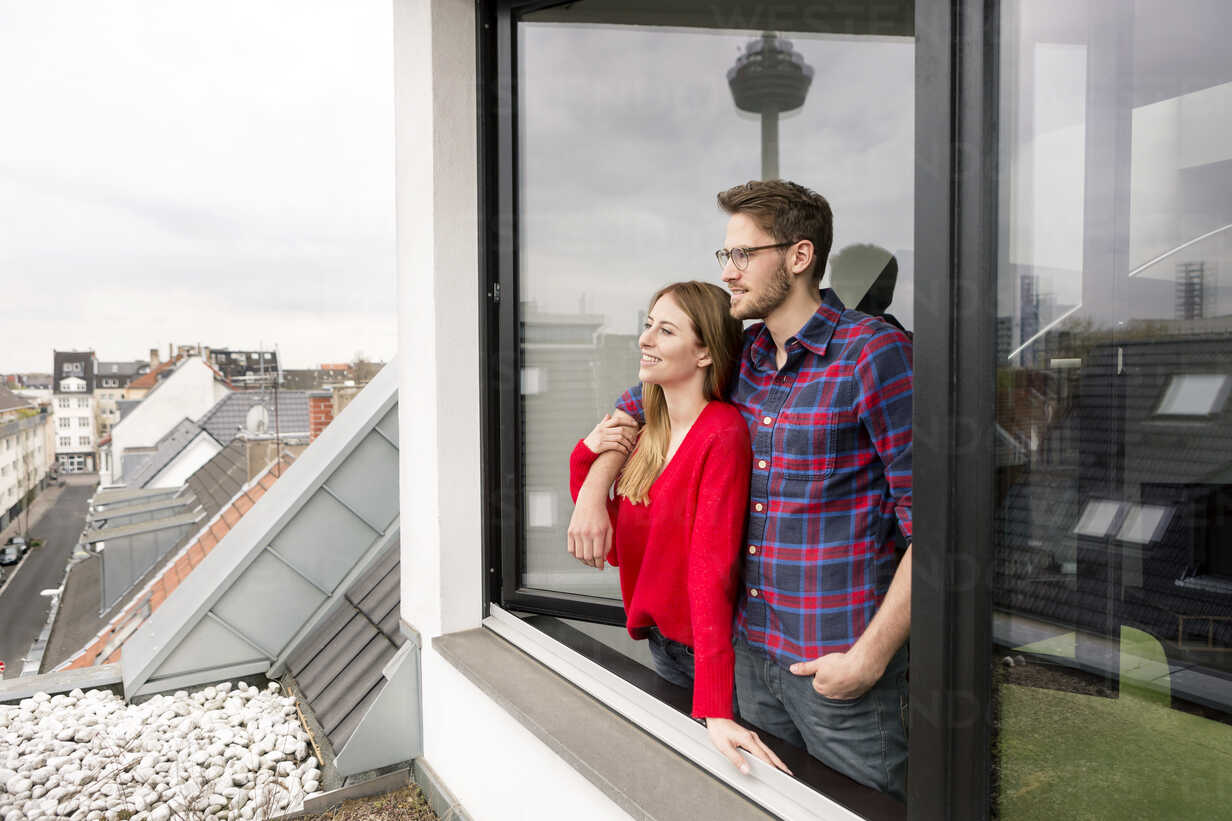 Smiling young couple looking out of window in city apartment - PESF00809 - Peter Scholl/Westend61