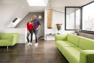Portrait of smiling young couple standing in living room at home - PESF00812