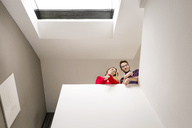 Portrait of smiling young couple on upper floor under roof window - PESF00815