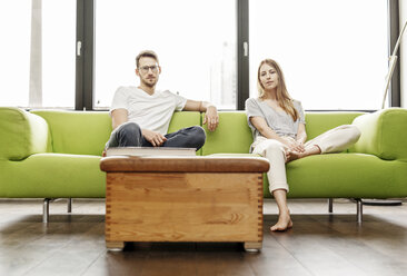 Portrait of serious young couple sitting on couch in living room at home - PESF00830