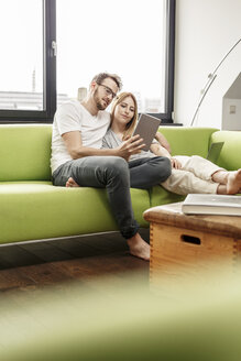 Smiling young couple on couch in living room at home sharing tablet - PESF00833