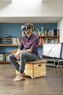 Young man at home sitting on box wearing VR glasses - PESF00839