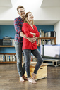 Happy young couple standing in living room at home embracing - PESF00842