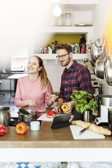 Happy young couple with tablet cooking together in kitchen - PESF00845