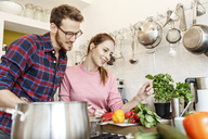 Happy young couple cooking together in kitchen - PESF00848