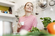 Smiling young woman with cup of espresso in kitchen at home - PESF00851