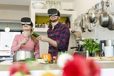 Happy young couple wearing VR glasses cooking together in kitchen - PESF00854
