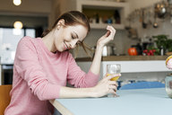 Smiling young woman with glass of orange juice in kitchen at home - PESF00857
