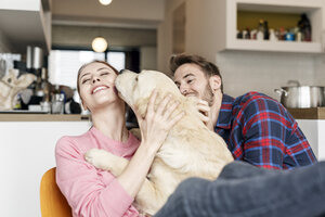 Happy young couple cuddling with dog at home - PESF00860
