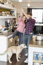 Young couple with dog dancing in the kitchen - PESF00863