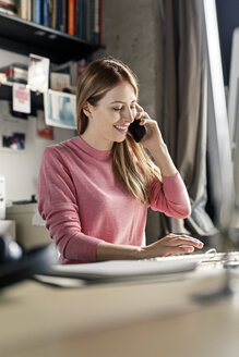 Smiling young woman on the phone at desk at home - PESF00878
