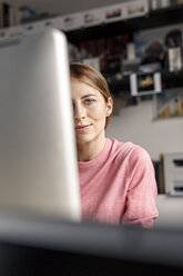 Portrait of young woman behind computer screen at desk at home - PESF00881