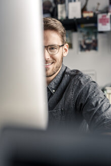 Portrait of smiling young man behind computer screen at desk at home - PESF00887