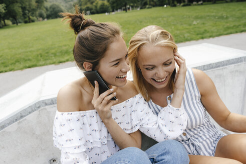 Two happy young women with cell phones in a skatepark - KNSF03056