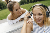 Two happy young women with headphones outdoors - KNSF03062