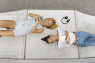 Two happy young women with cell phones lying on ramp in a skatepark - KNSF03065