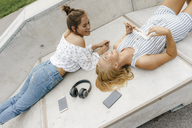 Two happy young women lying on ramp in a skatepark making music - KNSF03068