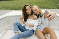 Two happy young women taking a selfie in a skatepark - KNSF03071