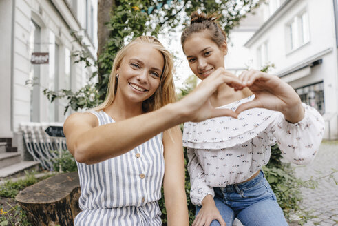 Two smiling young women shaping heart with their hands in the city - KNSF03089