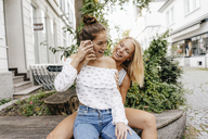 Two happy young women with cell phone in the city - KNSF03092