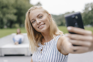 Portrait of smiling young woman taking a selfie in a skatepark - KNSF03119
