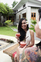 Portrait of woman with flower in her hair drinking a cocktail with friend in garden - IGGF00233