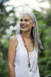 Attractive senior woman standing in nature, portrait - SBOF00926